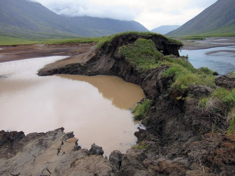 Permafrost is thawing across the Arctic, causing land surface to subside or change shape. In this photo taken on July 7, 2014 in Gates of the Arctic National Park, a bank of this lake thawed, allowing the Okokmilaga River to cut through and drain it to sea. Photo: National Park Service Climate Change Response.