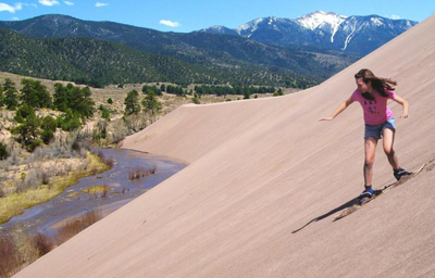 Girl sliding down a dune.
