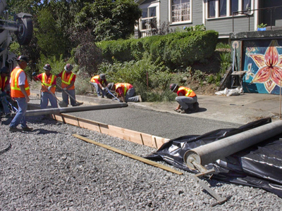 workers laying concrete that is porous