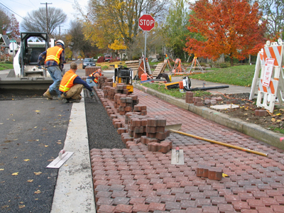 workers laying porous pavers