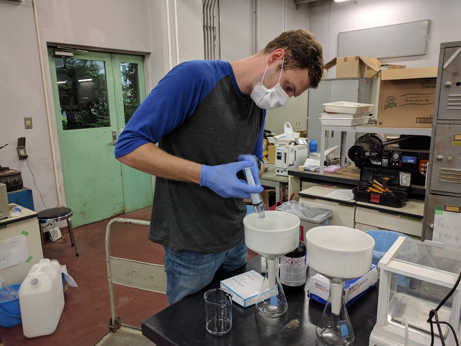 Student working in lab with soil samples.