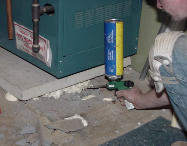Man sealing cracks in basement wtih a caulk gun