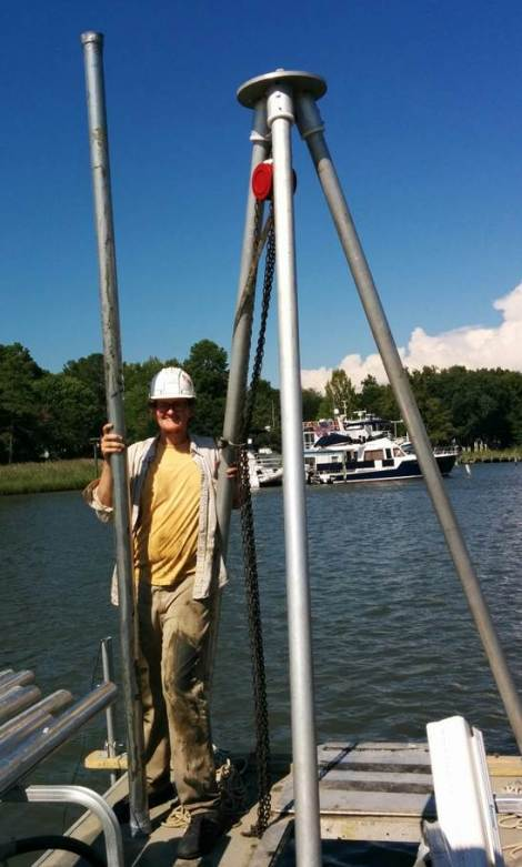 Man with hard hat and yellow shirt on boat with very large tripod and pipe for taking soil samples on a blue sky sunny day
