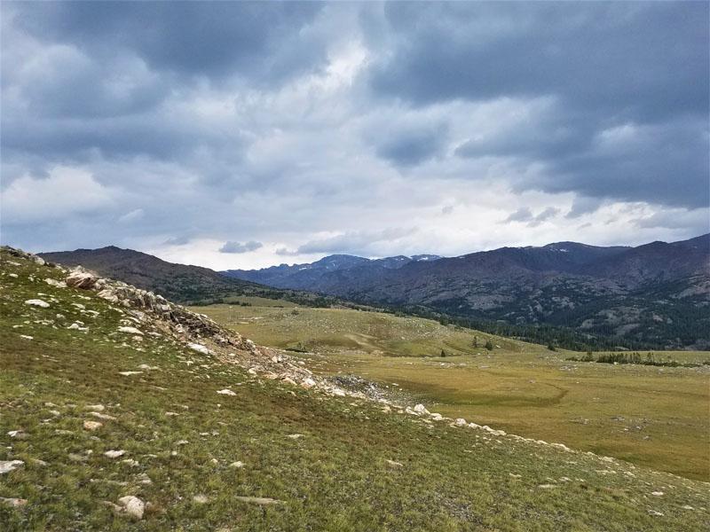 Foreground green grass. Mid photo a rdige of grey rocks. Distance mountain range. Sky dark grey clouds