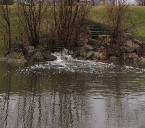 Hill with vent and water flowing out into large pond for holding water.