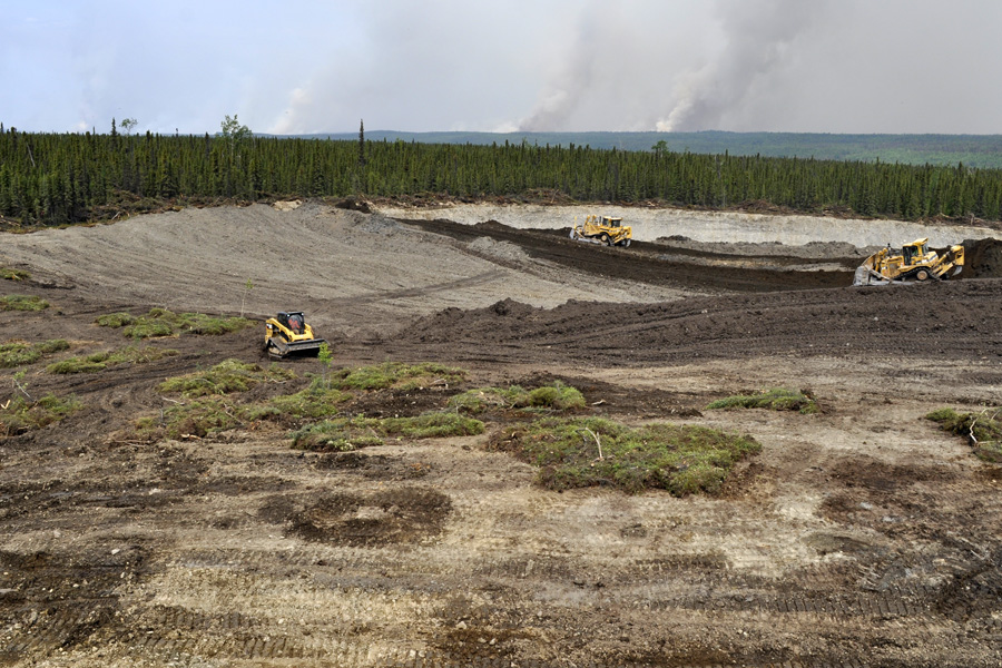 three yellow plows doing restoration work in foreground, plumes showing smoke in the distance