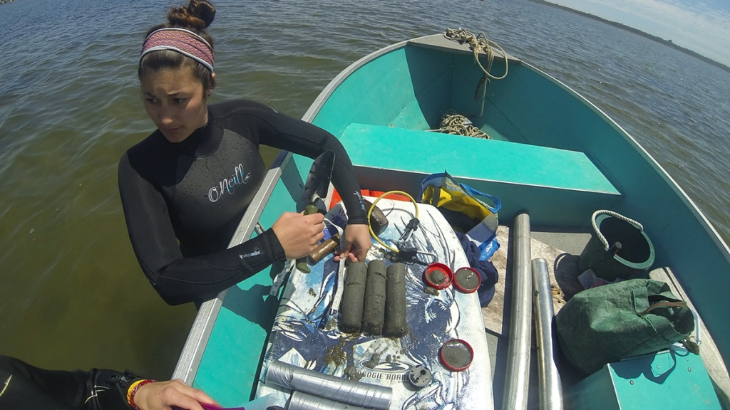 Scientist on the edge of a boat with equipment